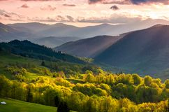 Gorgeous mountainous countryside at sunset. Beautiful landscape with purple sky over the forested rolling hills lit by sun rays Royalty Free Stock Photography