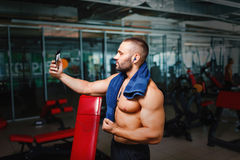 Sports man taking a selfie. Bodybuilder with towel after a workout. Athlete on a blurred gym background. Sport concept. Royalty Free Stock Photo