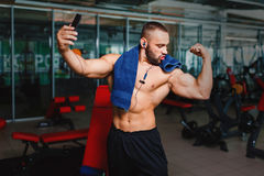 Sports man taking a selfie. Bodybuilder with towel after a workout. Athlete on a blurred gym background. Sport concept. A gorgeous and muscular man flexing and Stock Images