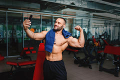 Sports man taking a selfie. Bodybuilder with towel after a workout. Athlete on a blurred gym background. Sport concept. A gorgeous and muscular man flexing and Royalty Free Stock Photo