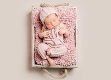Gorgeous newborn baby sleeping, top view. Gorgeous newborn baby in knitted clothes peacfully sleeping on pink rug, top view Royalty Free Stock Photos