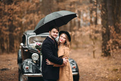 Gorgeous newlywed bride and groom posing in pine forest near retro car in their wedding day Royalty Free Stock Photo