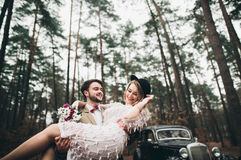 Gorgeous newlywed bride and groom posing in pine forest near retro car in their wedding day Royalty Free Stock Images