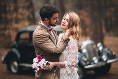 Gorgeous newlywed bride and groom posing in pine forest near retro car in their wedding day.  Royalty Free Stock Photo