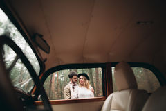 Gorgeous newlywed bride and groom posing in pine forest near retro car in their wedding day.  Stock Image