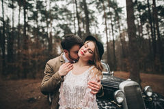 Gorgeous newlywed bride and groom posing in pine forest near retro car in their wedding day.  Royalty Free Stock Image