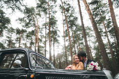 Gorgeous newlywed bride and groom posing in pine forest near retro car in their wedding day.  Stock Photography