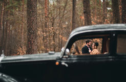 Gorgeous newlywed bride and groom posing in pine forest near retro car in their wedding day Stock Photos