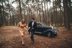 Gorgeous newlywed bride and groom posing in pine forest near retro car in their wedding day.  Royalty Free Stock Photos