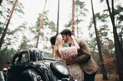 Gorgeous newlywed bride and groom posing in pine forest near retro car in their wedding day Stock Photo