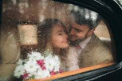 Gorgeous newlywed bride and groom posing in pine forest near retro car in their wedding day.  Royalty Free Stock Images