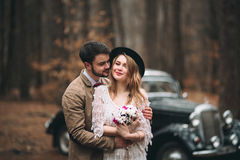 Gorgeous newlywed bride and groom posing in pine forest near retro car in their wedding day Stock Image