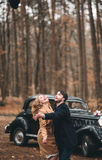 Gorgeous newlywed bride and groom posing in pine forest near retro car in their wedding day Royalty Free Stock Image