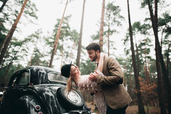 Gorgeous newlywed bride and groom posing in pine forest near retro car in their wedding day Stock Photography