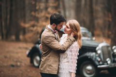 Gorgeous newlywed bride and groom posing in pine forest near retro car in their wedding day Stock Images