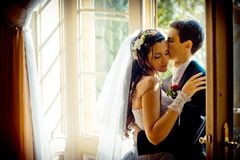 The gorgeous newlywed couple is tenderly hugging near the old open window. The handsome groom is softly kissing his. Adorable bride in the head Stock Photography