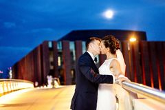 Gorgeous newlyweds on the city bridge at night. Night wedding session Stock Photo