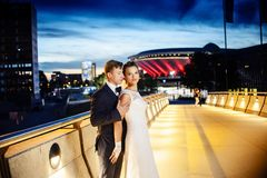 Gorgeous newlyweds on the city bridge at night. Night wedding session Royalty Free Stock Photography