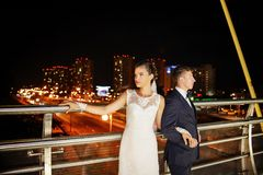 Gorgeous newlyweds on the city bridge at night. Night wedding session Stock Image