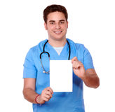 Gorgeous nurse man holding a white card Royalty Free Stock Photography