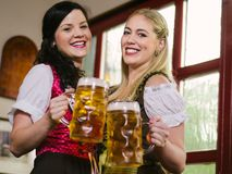 Gorgeous Oktoberfest waitresses with beer. Photo of two beautiful female waitresses wearing traditional dirndl and holding huge beers in a pub Royalty Free Stock Image