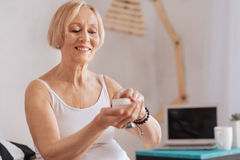Gorgeous old woman opening bottle of cream. Open it. Delighted senior female holding arms bent in elbows keeping smile on her face while being in good mood Stock Photos