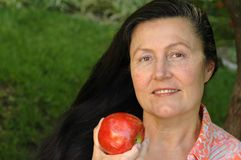 Gorgeous older woman eating an. Very attractive older woman enjoying an apple in her garden.  Healthy senior lifestyle concept Royalty Free Stock Image