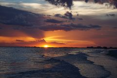 A gorgeous orange sky at sunset in Ft.Myers Beach, Florida as the waves roll onto the shore. A gorgeous orange sky as the sun sets over the ocean with waves Royalty Free Stock Photos