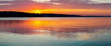Gorgeous orange teal sunset on huge calm lake royalty free stock images