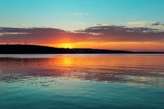 Gorgeous orange teal sunset on huge calm lake royalty free stock photography