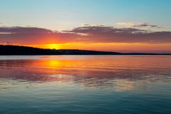 Gorgeous orange teal sunset on huge calm lake royalty free stock image