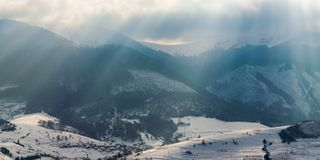 Gorgeous panorama of mountains in winter. Snowy hills lit with sun light through overcast sky. small village in the distant valley stock photo