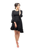 Gorgeous passionate Hispanic woman in black dress walking and looking away. Stock Photos