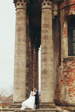 A gorgeous picture of newlyweds standing behind an old half-ruin Stock Photography