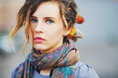 Gorgeous portrait of a young serious girl with beautiful blue eyes and youthful hair in the scarf   color picture Stock Photos
