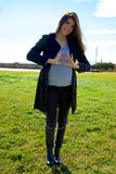 Gorgeous pregnant woman showing love sign on belly in park wide shot Royalty Free Stock Photos
