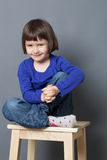 Gorgeous preschool child sitting in holding crossed legs. Kid wellbeing concept - gorgeous preschool child sitting in holding her crossed legs and hands ready to stock photography