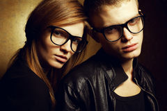 Gorgeous red-haired fashion twins in black clothes. Eyewear concept. Portrait of gorgeous red-haired fashion twins in black clothes wearing trendy glasses and Royalty Free Stock Images