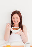 Gorgeous red-haired female having her breakfast royalty free stock image