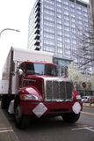 Gorgeous red semi truck with traler on urban city street Stock Photography