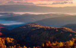 Gorgeous red sunrise in mountains. Forested hills in colorful fall foliage. fog in the distant valley royalty free stock photos