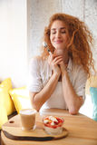 Gorgeous redhead young lady sitting in cafe while eating dessert. Royalty Free Stock Photography