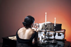 Gorgeous retro woman before voyage. Retro woman before voyage with mirror in hand Stock Image