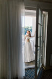 Gorgeous romantic bride in white dress and veil posing at hotel balcony.  royalty free stock photo