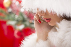Gorgeous Santa girl speaking on phone. Portrait of a gorgeous Santa girl speaking on the phone with her face almost hidden under white fur of her Santa hat Royalty Free Stock Photo