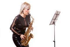 Attractive saxophonist woman playing at her musical instrument Stock Photography