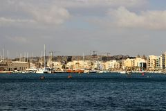 Gorgeous sea view of one of the bays of the island of Malta. Calm blue sea, numerous white yachts, a city on the other side, modern residential buildings stock images