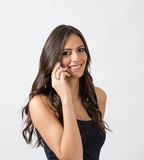 Gorgeous sensual long hair beauty smiling at camera while talking on the cellphone Stock Photos