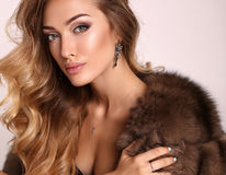Gorgeous sensual woman with blond hair in luxurious fur coat Stock Photos