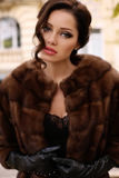 Gorgeous sensual woman with dark hair in luxurious fur coat and leather gloves royalty free stock image
